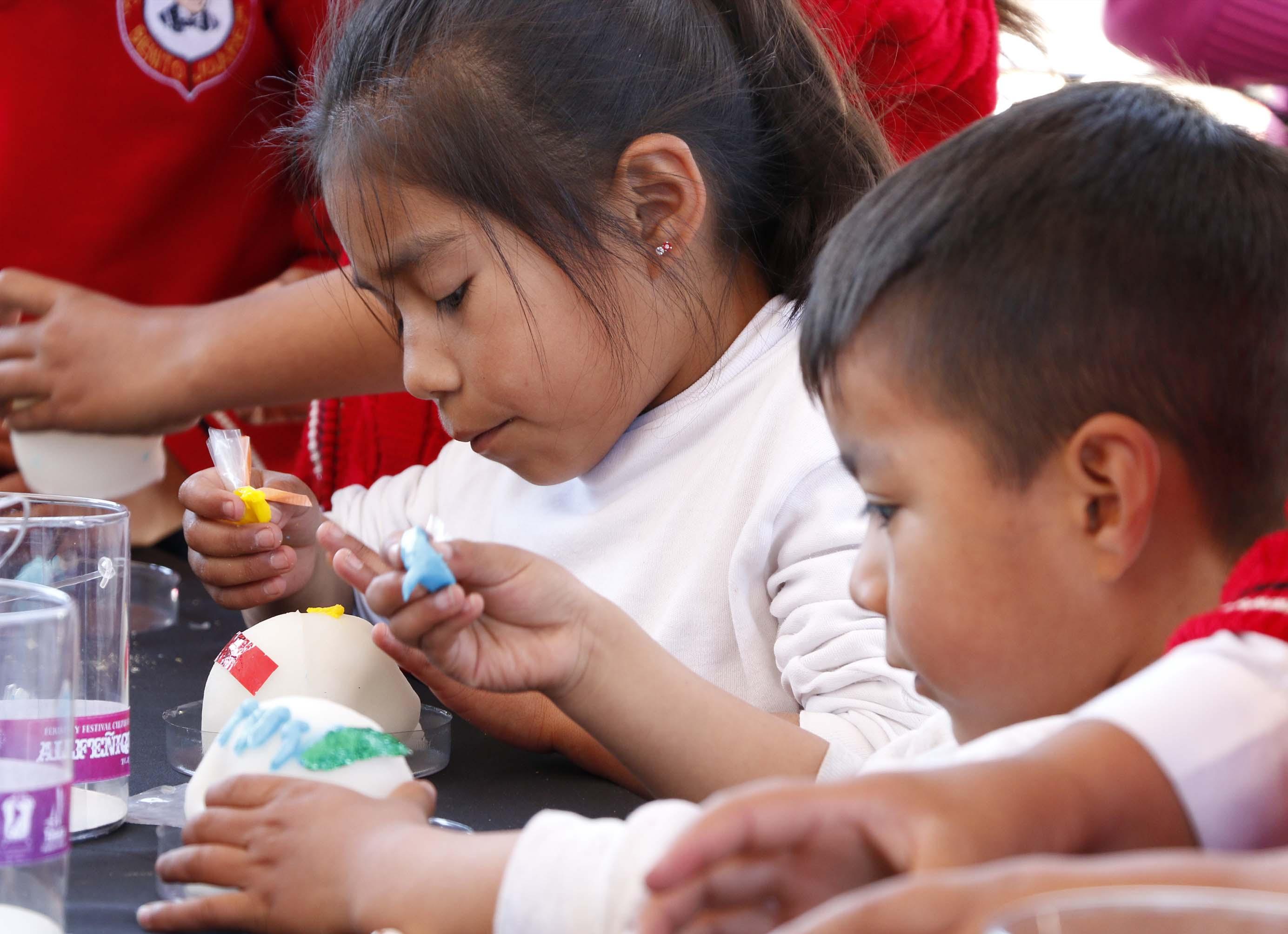 En Toluca niños de todas las edades decoran calaveras de alfeñique