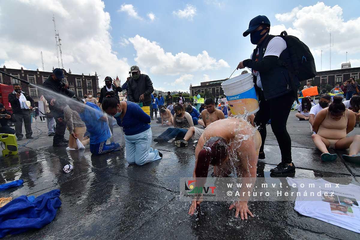 Un grupo de personas es rociada con agua durante un performance para denunciar malos tratos a presos en penales del Estado de México